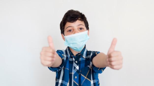 Okの標識を示すマスクを持つ少年 無料写真