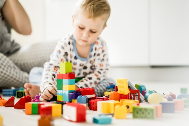 Boy with mom playing in colorful building kit Free Photo