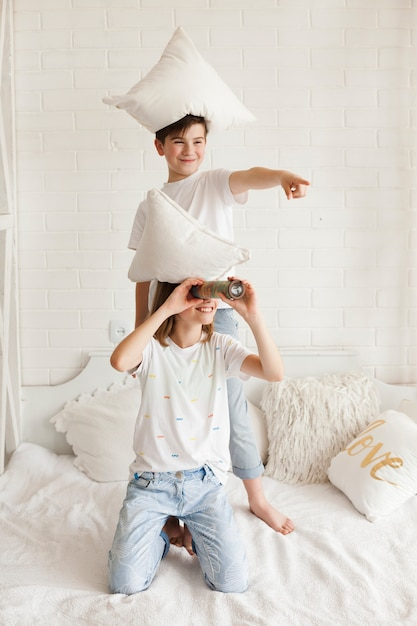 Boy with pillow on head pointing at something while her sister looking through telescope Free Photo