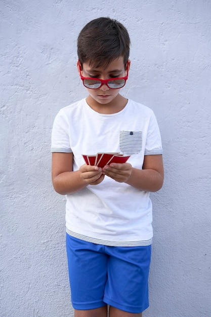 Premium Photo Boy With Red Sunglasses Playing Poker