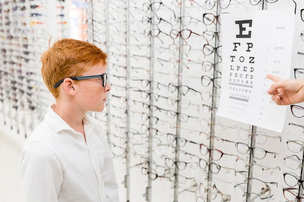 Boy with spectacle looking at snellen chart while doctor's hand pointing at chart Free Photo