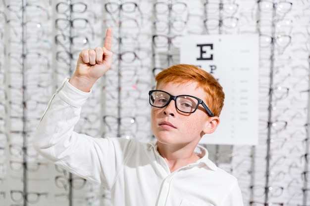 Boy with spectacle pointing at upward direction standing against eyeglasses display background Free Photo