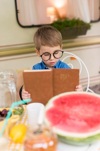 テーブルで読んでサングラスを持つ少年 無料写真