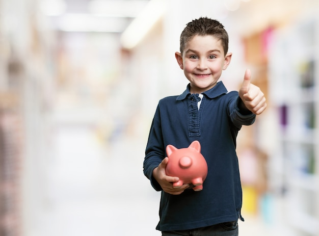 Boy with thumb up and a piggy bank Free Photo