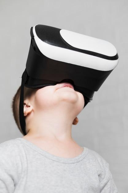 見上げる仮想ヘッドセットを持つ少年 無料写真