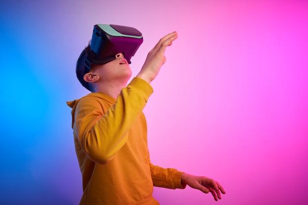 Мальчик с очками виртуальной реальности на красочном фоне. технологии будущего, концепция vr Premium Фотографии