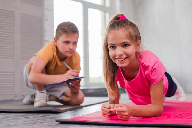 Boy writing on clipboard while looking at smiling girl exercising Free Photo