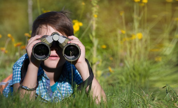 Boy young researcher exploring with binoculars environment in summer garden Premium Photo