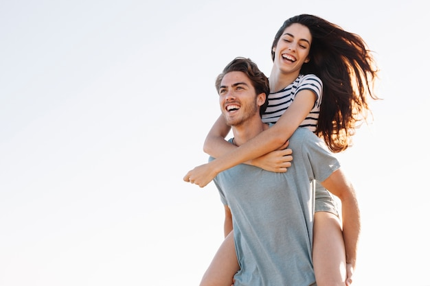 Boyfriend carrying laughing girlfriend at the beach Free Photo