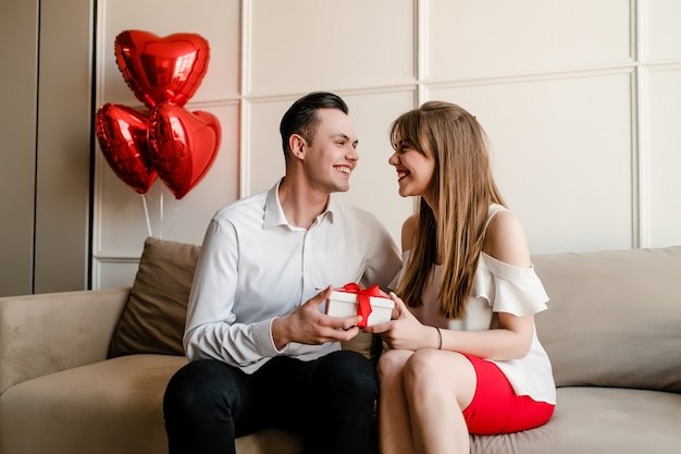 Boyfriend and girlfriend exchange romantic gifts on couch with heart shaped balloons at home Premium Photo