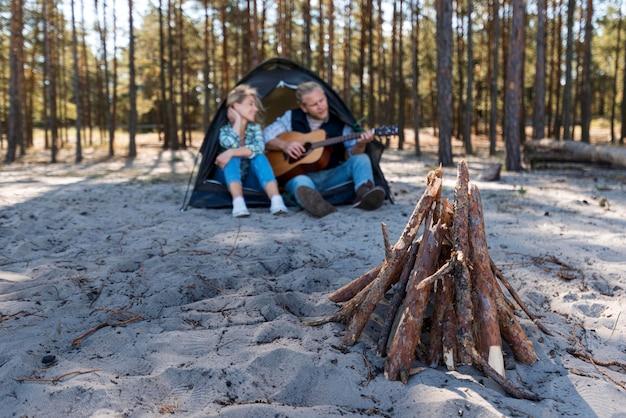 Бойфренд играет на акустической гитаре и у костра Бесплатные Фотографии