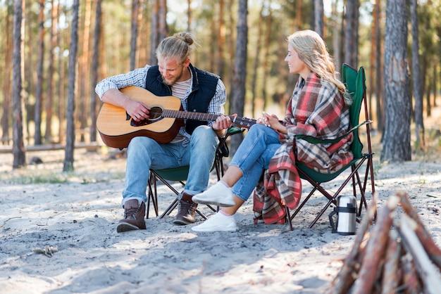 Парень играет на акустической гитаре на открытом воздухе Бесплатные Фотографии
