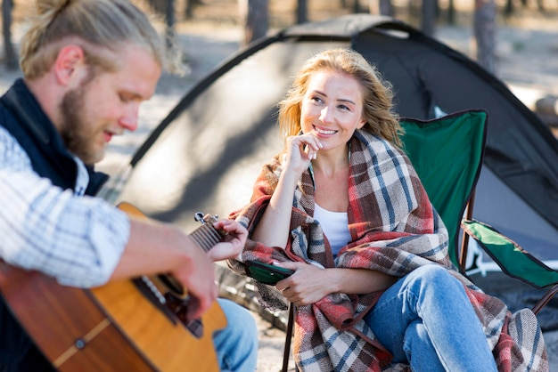 Ragazzo che suona la chitarra acustica vista frontale della donna Foto Gratuite