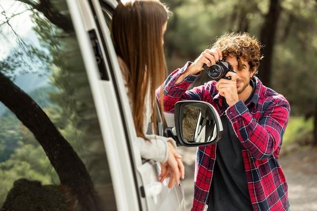 도로 여행 중에 차에서 여자 친구의 사진을 찍는 남자 친구 무료 사진