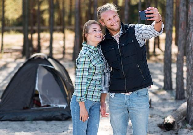 Fidanzato che prende un selfie con la loro tenda nella parte posteriore Foto Gratuite