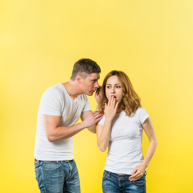 Boyfriend telling surprising secret to his girl's ear against yellow background Free Photo