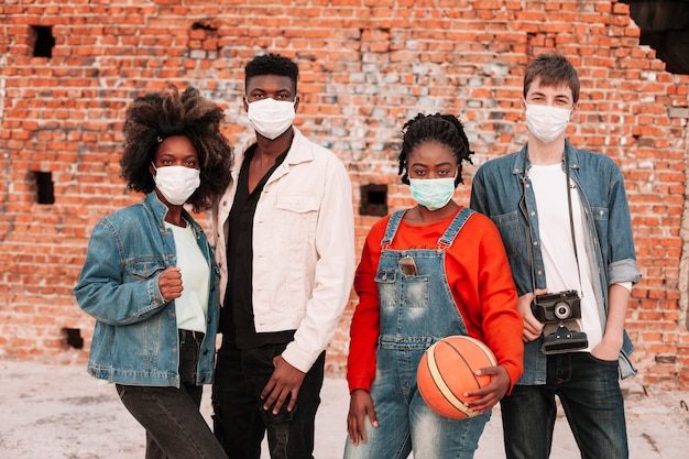 Ragazzi e ragazze in posa con maschere chirurgiche Foto Gratuite