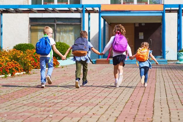 Boys and girls running to the elementary school. Premium Photo