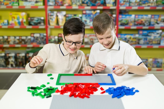 Boys play together with colored plastic blocks in the gaming center, school. Premium Photo