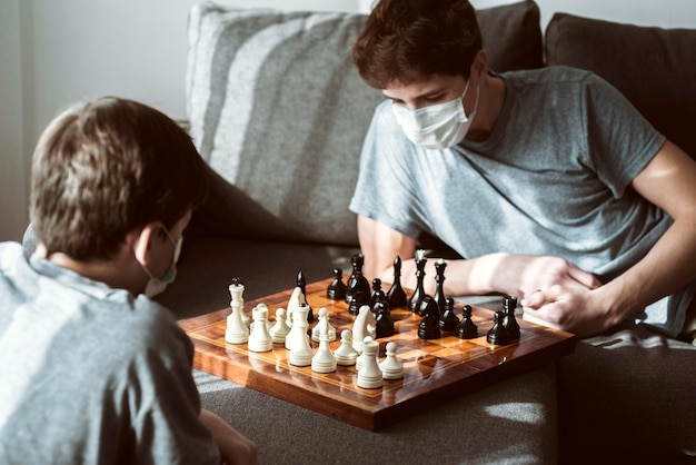 Boys playing chess at home while being quarantined Free Photo