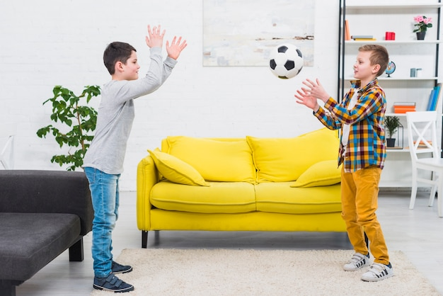 Boys playing football in living room Free Photo