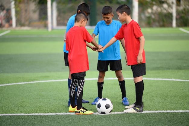 Мальчики играют в футбол на футбольном тренировочном поле | Премиум Фото