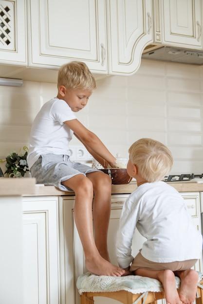 Мальчики заранее испечь домашний пирог на кухне. два брата куки Premium Фотографии