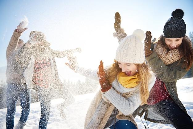 Ragazzi che lanciano palle di neve proprio sulle ragazze Foto Gratuite