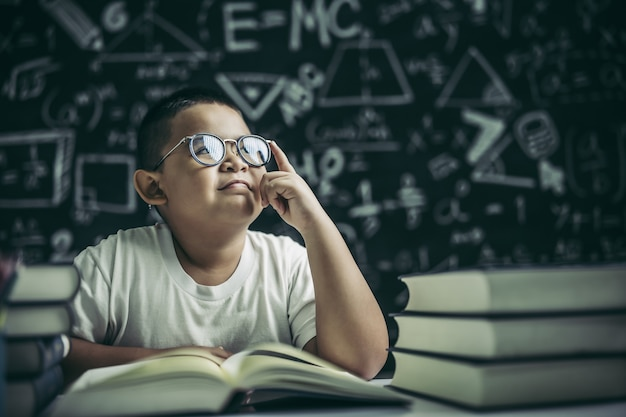 Boys with glasses write books and think in the classroom Free Photo