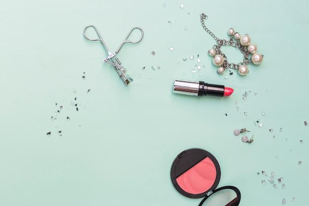 Bracelet; earrings lipstick; blusher and eyelash curlers on pastel backdrop Free Photo