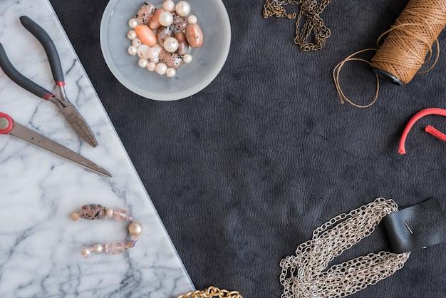 ビーズで作られたブレスレット。鎖;糸巻きペンチと織り目加工の背景にはさみ Premium写真