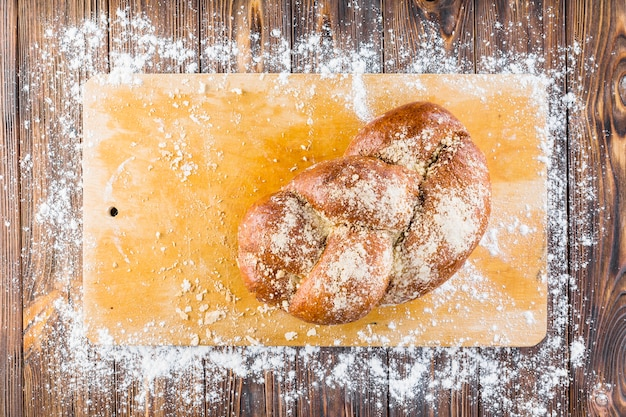 Braided bread on chopping board with spread white flour Free Photo