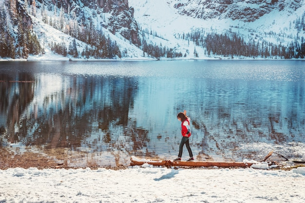 ドロミテの山湖braiesを歩いている女性とカラフルな冬の風景。 Premium写真