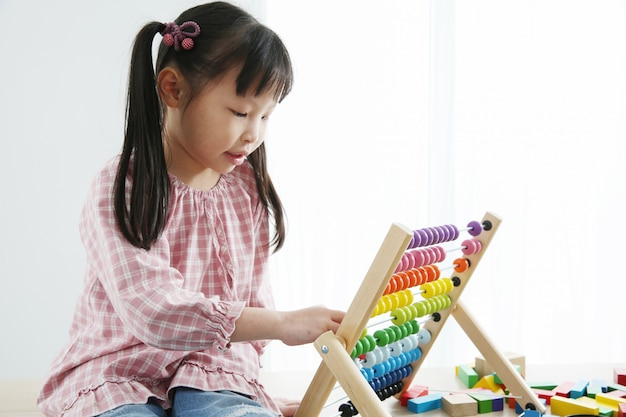 Brain development at early childhood with the abacus. kindergarten children grabbing colorful wooden abacus Premium Photo