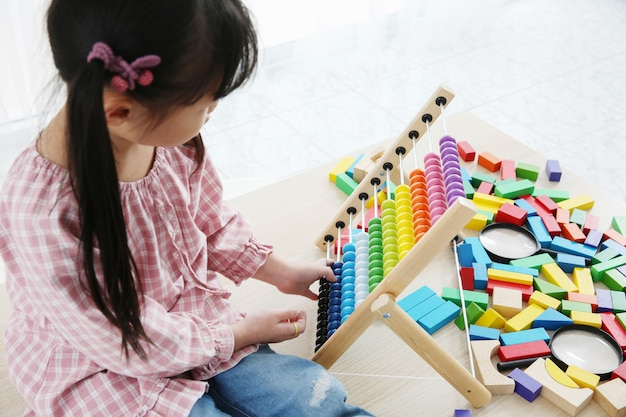 Brain development at early childhood with the abacus. kindergarten children grabbing colorful wooden abacus. Premium Photo