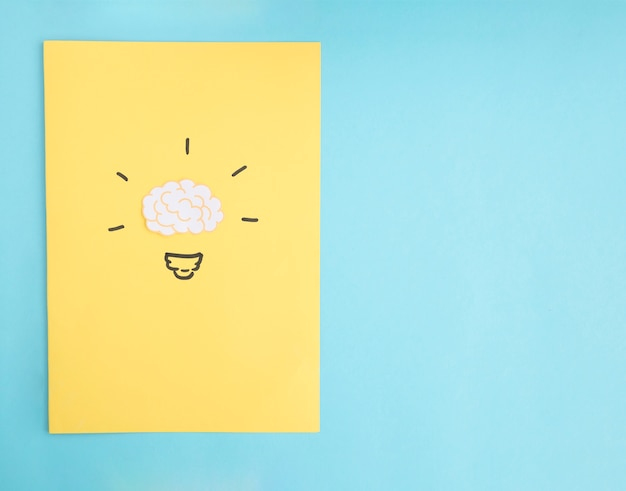 Brain idea light bulb on yellow paper over the blue backdrop Free Photo