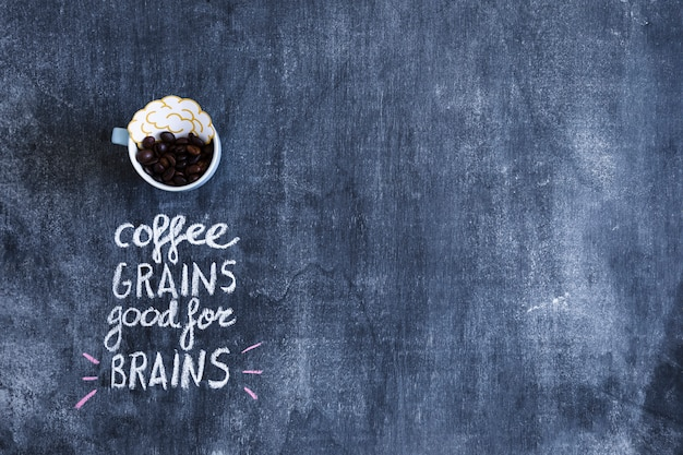 Brain paper cutout and coffee beans in cup with text on chalkboard Free Photo