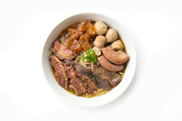 Braised beef clear soup with noodle(kuay taiw nuae toon) in bowl top view on white background Premium Photo