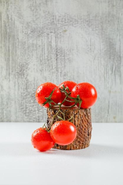 灰色の汚れたと白い表面に木製のカッティングピース側ビューでジューシーなトマトの枝 無料写真