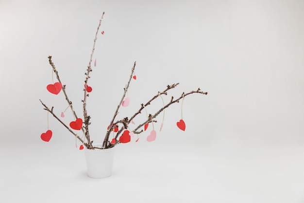 Branches of a plant in a white flowerpot with hanging hearts Free Photo