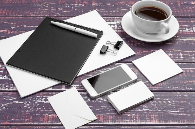 紫色の机の上の文房具のモックアップのブランディング。紙、名刺、パッド、ペン、コーヒーの平面図。 Premium写真