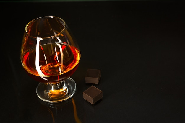 Brandy glass and chocolate on black background Premium Photo