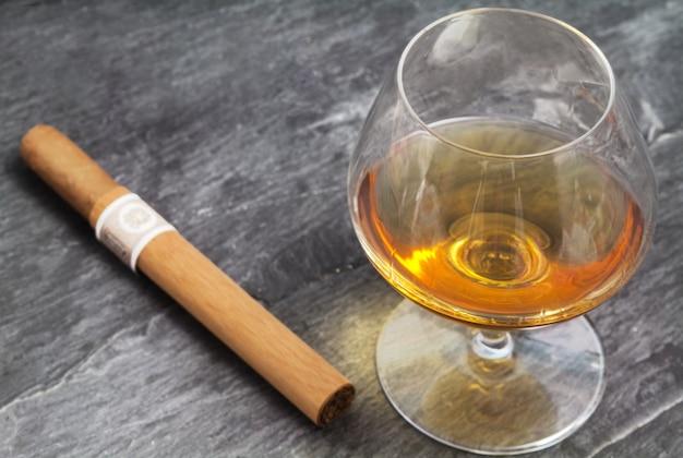 Brandy glass and cigar over ardesia Premium Photo
