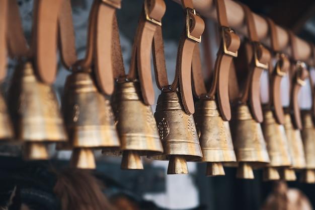 Снаружи на кожаных ремешках висят латунные колокольчики в ряд в перспективе. закрыть вверх Premium Фотографии