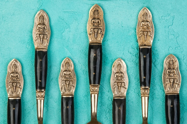 Brass spoons, forks and knives on concrete background. Premium Photo