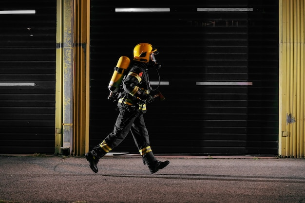 Brave fireman in protective uniform with full equipment running to taking care of fire. Premium Photo