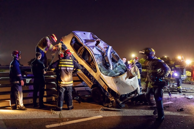 Brave firemen trying to release man from crashed car. Premium Photo