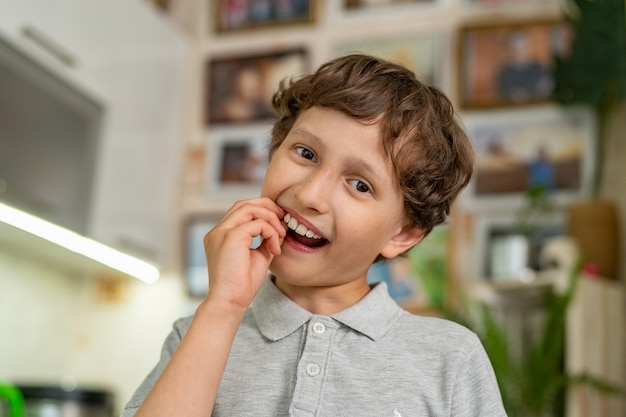 A brave little boy of 7 years old shakes his baby tooth. Premium Photo