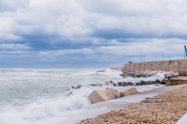 Brave waves of the adriatic sea beating against the breakwater of the seafront in bari, italy Premium Photo
