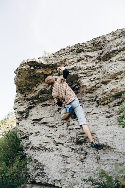 Brave young man climbs the cliff Premium Photo